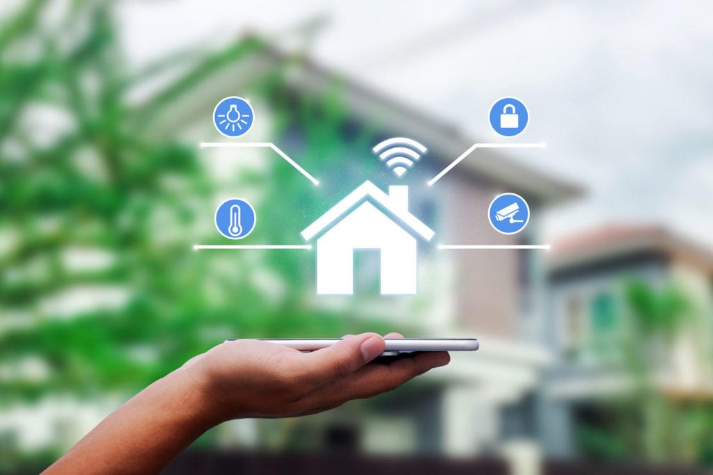 Mão segurando celular com ícones digitais em frente a uma casa
